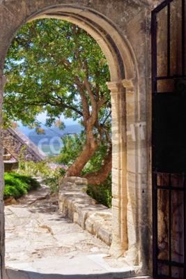 Fototapeta Obejrzyj przez otwarte drzwi na wewnętrznym dziedzińcu średniowiecznego zamku Barroux. Prowansja, Francja