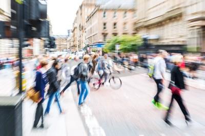 obraz z efektem kreatywnego powiększenia zrobiony aparatem tłumu ludzi przekraczających ulicę miasta