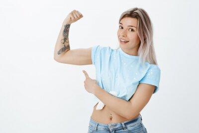 Oczywiście możesz mnie pokonać, spójrz na ten mięsień. Radosna pozytywna atrakcyjna kobieta z wielkim ciałem, podnosi tatuującą rękę i wskazuje przy bicepsami z palcem wskazującym, pracującym i prowad