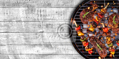 Fototapeta Odgórny widok świeży mięso i warzywo na grillu umieszczającym na drewnie