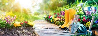 Fototapeta Ogrodnictwo - zestaw narzędzi do Ogrodnik i Doniczki w słonecznym ogrodzie