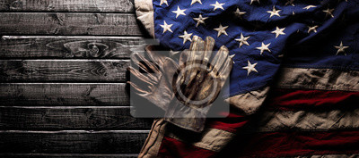 Fototapeta Old and worn work gloves on large American flag - Labor day background