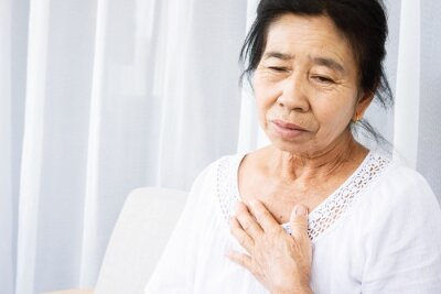 Fototapeta old Asian woman having problem with shortness of breath, difficult breathing hand touching her chest