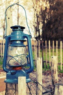 Fototapeta Old blue kerosene lamp hangs on wooden outdoor fence