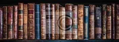 Fototapeta Old books on wooden shelf. Tiled Bookshelf background.  Concept on the theme of history, nostalgia, old age. Retro style.