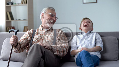 Fototapeta Old man and boy laughing genuinely, joking, valuable fun moments together