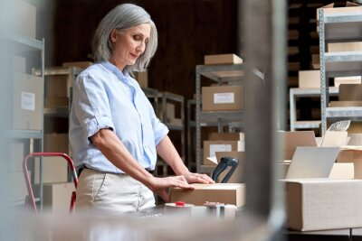Fototapeta Older mature female online store small business owner worker packing package post drop shipping ecommerce retail order in box preparing delivery parcel on table in warehouse. Dropshipping service.