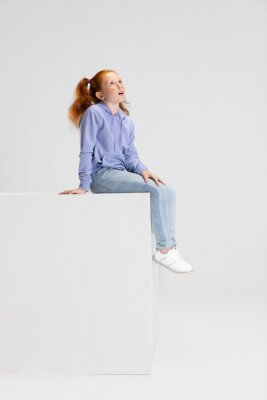Fototapeta One cute red-headed girl in casual clothes sitting on big box isolated on white studio background. Happy childhood concept. Sunny child. Looks happy, delighted