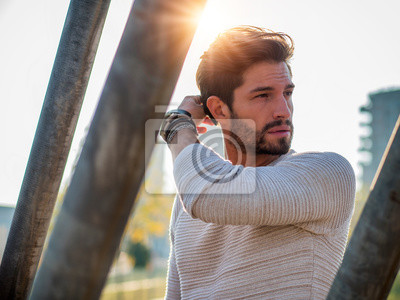 Fototapeta One handsome young man in urban setting in European city, standing