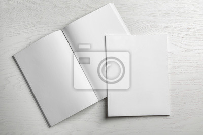 Fototapeta Open and closed blank brochures on wooden background, top view. Mock up for design