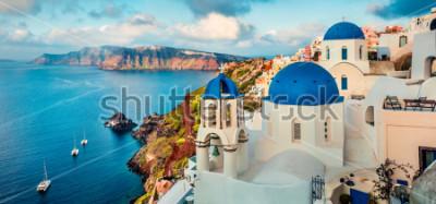 Fototapeta Oszałamiająco ranek panorama Santorini wyspa. Prześwietny wiosna wschód słońca na sławnym Greckim kurorcie Oia, Grecja, Europa. Podróże koncepcja tło. Styl artystyczny po przetworzeniu zdjęcia.