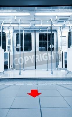 Fototapeta Oto drzwi otwarte w stacji metra z czerwoną strzałką na ziemi.