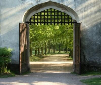 Fototapeta Otwarta brama zamku z kratkami do grillowania i widok na piękny ogród pełen drzew