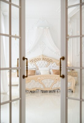 Fototapeta Otwarte drzwi prowadzące do białej klasycznej sypialni