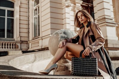 Fototapeta Outdoor full-length portrait of young elegant woman wearing beige trench coat, heels, posing with classic black tweed bag, handbag. Copy, empty space for text. Autumn fashion advertising concept.