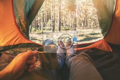 Fototapeta outdoor tourism - man laying in tent with cup of tea