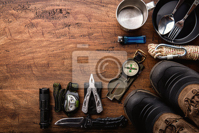 Fototapeta Outdoor travel equipment planning for a mountain trekking camping trip on wooden background. Top view - vintage film grain filter effect styles