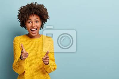 Fototapeta Outgoing carefree woman makes finger pistols, points directly at camera with positive expression, says I choose you, wears casual outfit, stands over blue wall with blank space area. You are my type