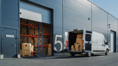 Fototapeta Outside of Logistics Warehouse with Open Door, Delivery Van Loaded with Cardboard Boxes. Truck Delivering Online Orders, Purchases, E-Commerce Goods, Wholesale Merchandise.