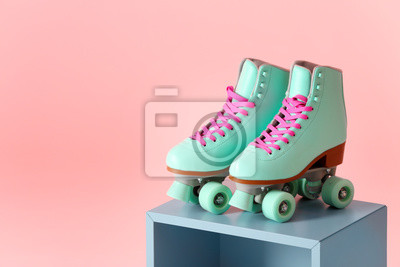 Fototapeta Pair of vintage roller skates on storage cube against color background. Space for text