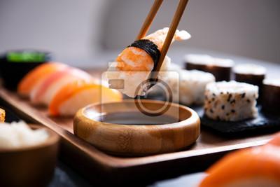 Fototapeta Pałeczka do jedzenia z kawałkiem sushi nigiri