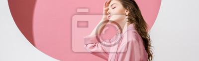 Fototapeta panoramic shot of beautiful girl touching hair on white and pink