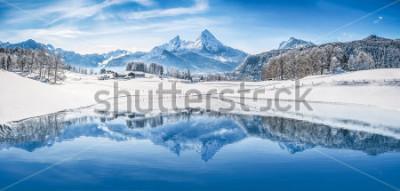 Fototapeta Panoramiczny widok na piękną zimową scenerię cudów zimowych w Alpach ze śnieżnymi szczytami górskimi odbijającymi się w krystalicznie czystym górskim jeziorze w zimny słoneczny dzień z błękitnym niebe
