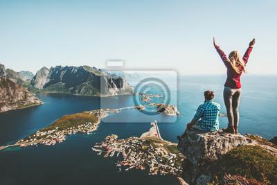 Fototapeta Para rodzina podróżujących razem na krawędzi klifu w Norwegii koncepcja życia mężczyzny i kobiety letnie wakacje odkryty widok z lotu ptaka Lofoten wyspy Reinebringen góra góry