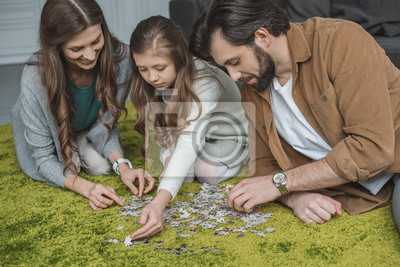 Fototapeta Parents And Daughter Connecting Puzzle Pieces On Carpet In Living Na Wymiar Zielony
