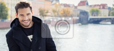 Fototapeta Paronamic zdjęcia z przystojny mężczyzna w płaszczu uśmiecha