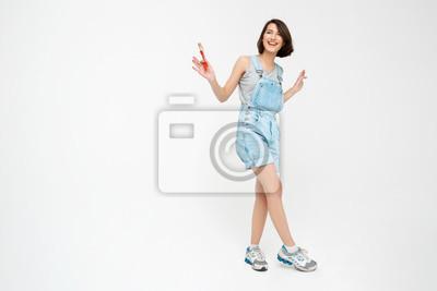 Pełna długość portret laughing ładną dziewczyną, trzymając malowanie