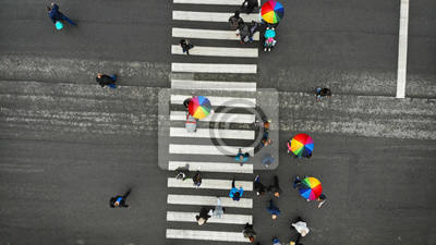 People crowd crossing a pedestrian crosswalk in a nasty day. Some of them with colorful umbrella. Top view.