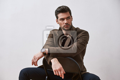 Fototapeta Perfect style. Stylish dark-haired man sitting on a chair and looking away isolated over white studio background