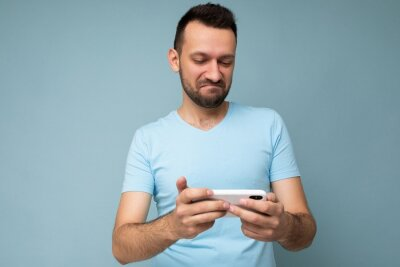Fototapeta Photo of asking handsome young man with beard wearing everyday blue t-shirt isolated over blue background holding and using mobile phone communication online on the internet looking at gadjet display