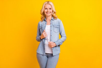 Fototapeta Photo of attractive positive old woman hands denim jeans shirt smile enjoy isolated on yellow color background