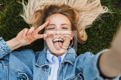Fototapeta Photo of blonde pretty woman taking selfie photo and showing peace sing while lying green grass in park