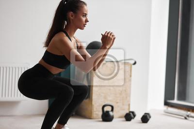 Fototapeta Photo of slim fitness model in black sportswear isolated on white background
