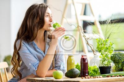 Fototapeta Pi? Kna kobieta siedzi z napojami i zdrowych zielonych? Ywno? Ci w domu. Wegańskie posiłki i koncepcja detox