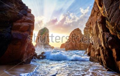 Fototapeta Piasek plaża wśród skał na wieczór zmierzchu. Ursa plaża blisko przylądka Roca (Cabo da Roca) przy Atlantyckim oceanu wybrzeżem w Portugalia. Letni krajobraz.