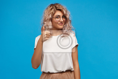 Fototapeta Picture of good looking friendly young Caucasian female wearing stylish clothes and round eyeglasses making approval gesture, showing thumbs up sign at camera and smiling happily, posing at blue wall