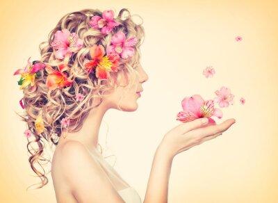Fototapeta Piękna dziewczyna podejmuje piękne kwiaty w dłoniach