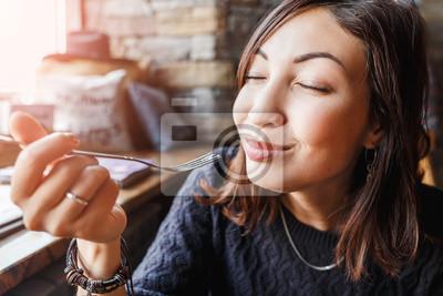 Fototapeta piękna młoda kobieta azjatyckich siedzi w kawiarni i jedzenie pyszne ciasto