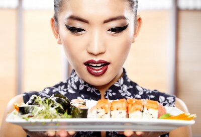 Fototapeta Piękna młoda kobieta jedzenia sushi. Płytkie głębi pola, focu