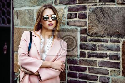 Fototapeta Piękna modelka kobieta nosi okulary i stojącej w pobliżu ściany z cegły