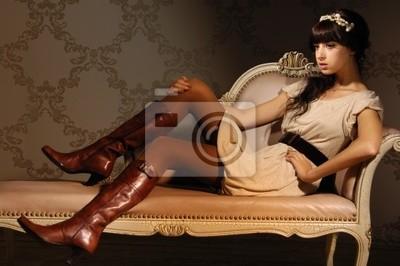 Piękna modelka siedzi na kanapie luksusowe
