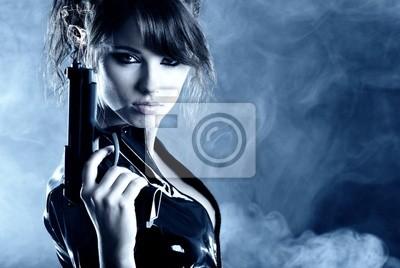 Fototapeta piękna seksowna dziewczyna trzyma pistolet. dym tle