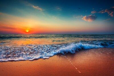 Fototapeta Piękne wschód słońca nad morzem i łamanie fali oceanu