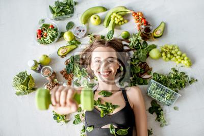 Fototapeta Piękno portret sportowej kobiety otaczającej różnorodnym zdrowym jedzeniem kłama na podłoga. Koncepcja zdrowego odżywiania i sportowego stylu życia