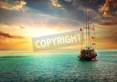 Fototapeta Piękny zachód słońca nad jachtem w morzu
