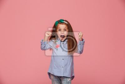 Fototapeta Piękny żeński dzieciak w włosianych obręczu i mody ubraniach zaciska pięści krzyczy z szczęściem i podziwem przeciw różowemu tłu